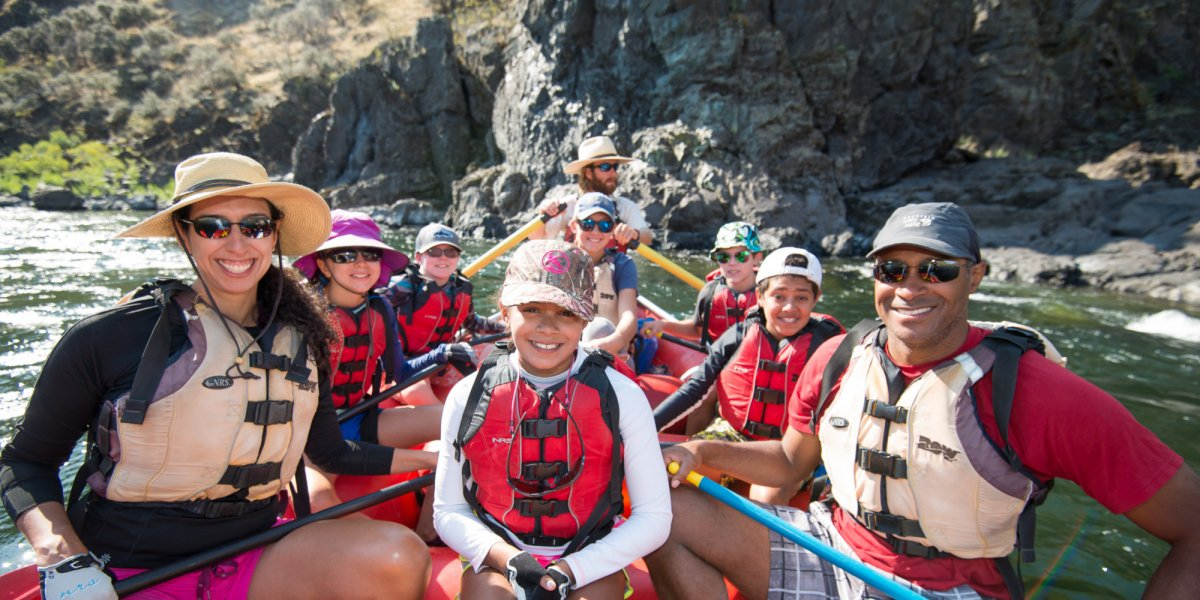 a family posing for a picture while river rafting
