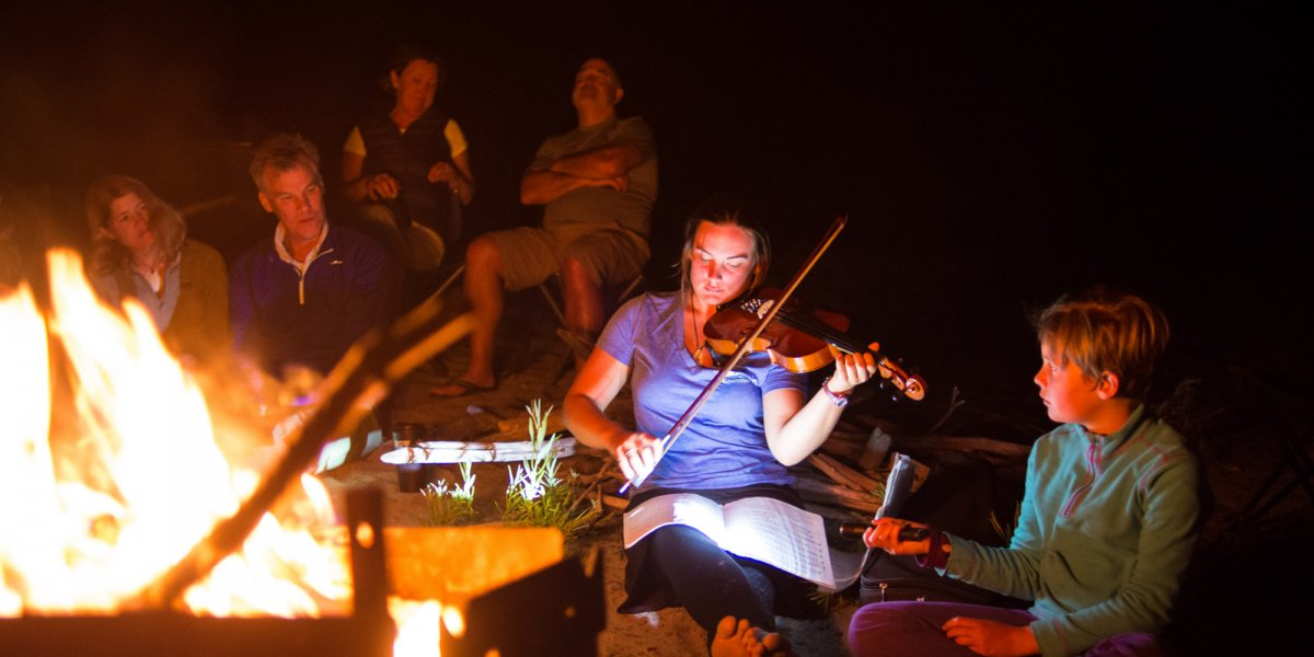 girl playing the violin while camping