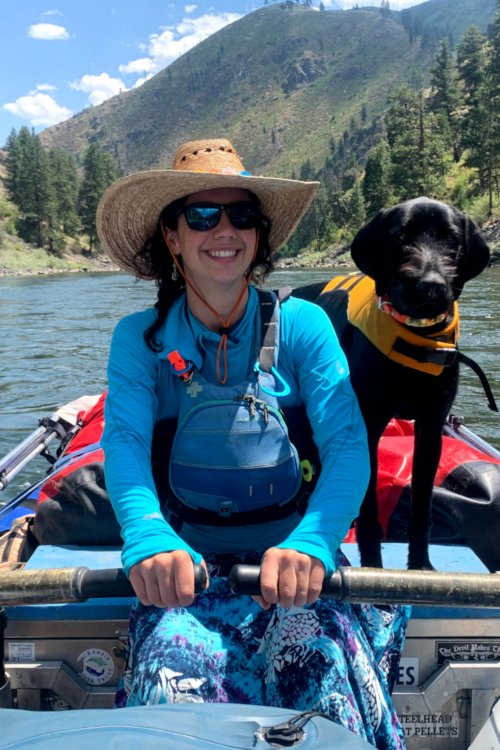 female river guide with dog on raft