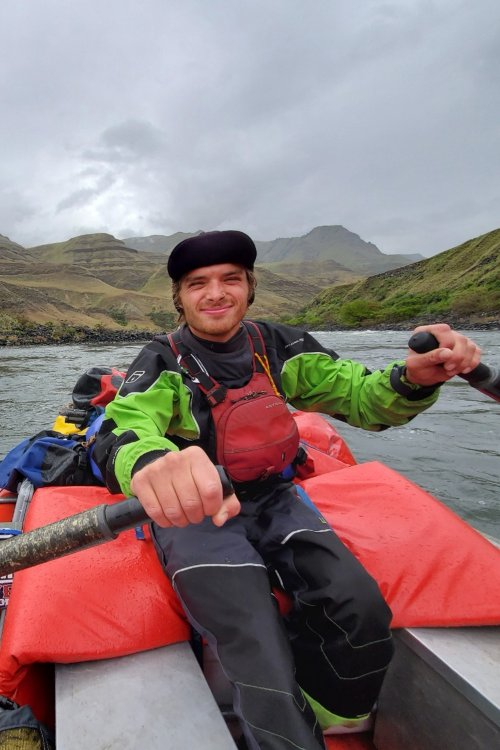 man rowing a raft down a river