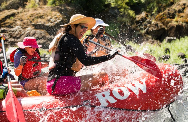 woman smiling on red raft going through white water