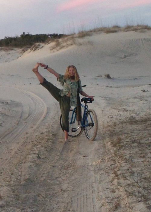 girl posing with a bike on a sandy trail