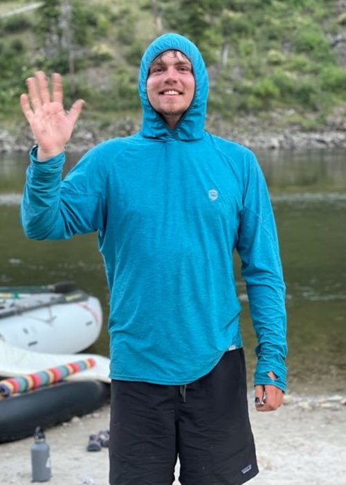river guide in blue hoodie along a river