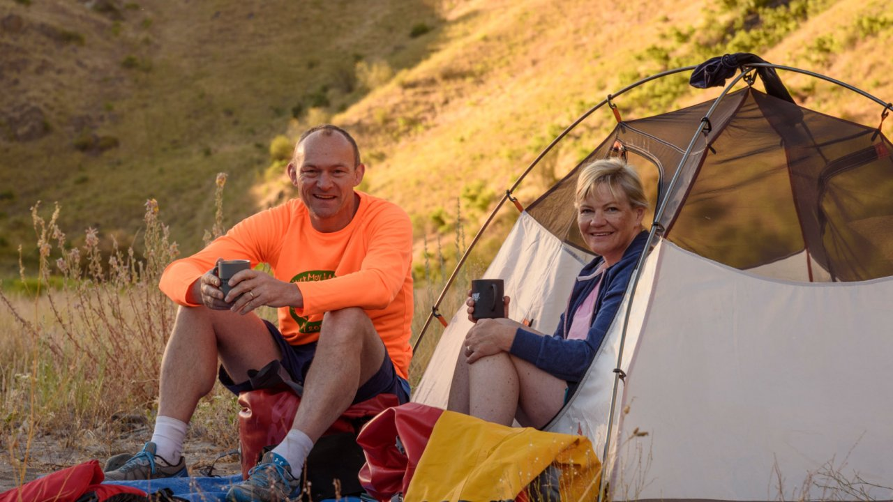 couple in tent along snake river