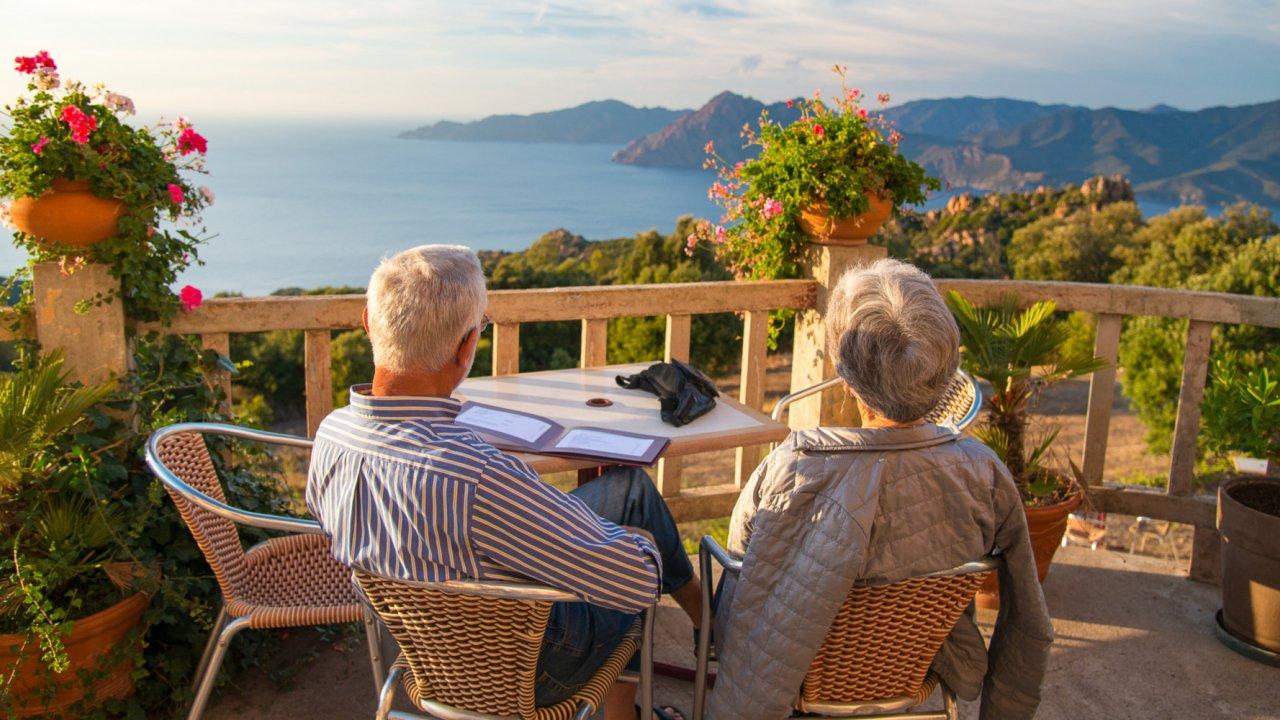 couple overlooking ocean from balcony in corsica
