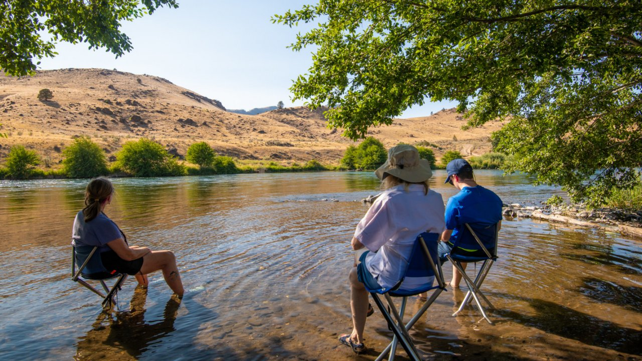 people sitting on chairs in river