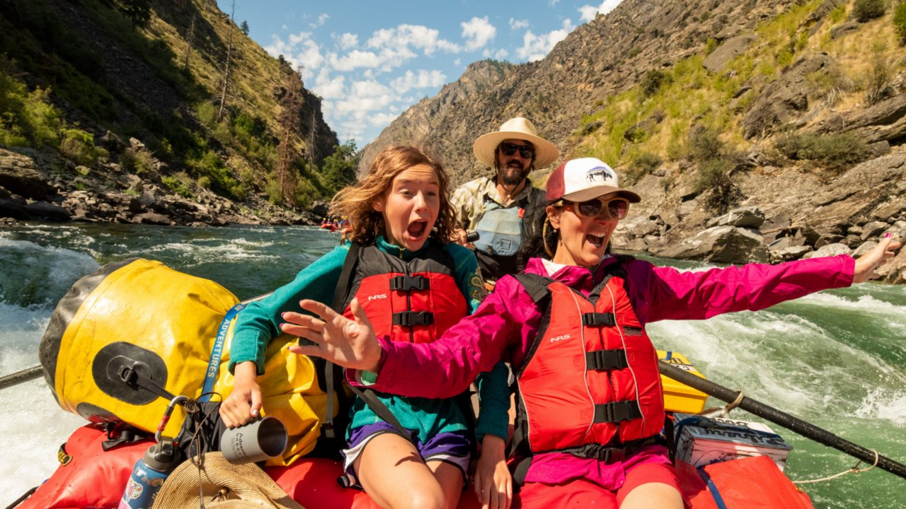 women on the front of a whitewater raft