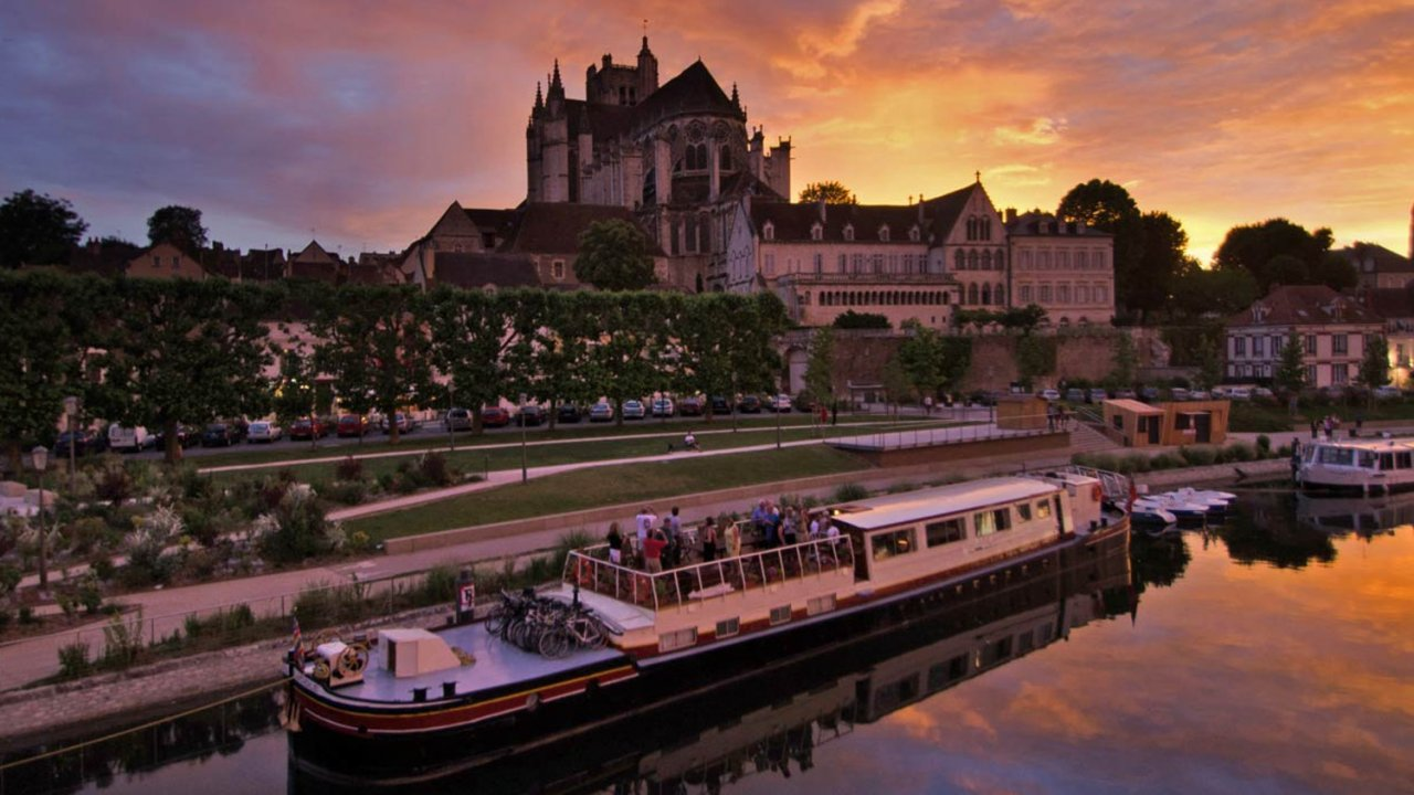 barge sitting in front of french city at sunset