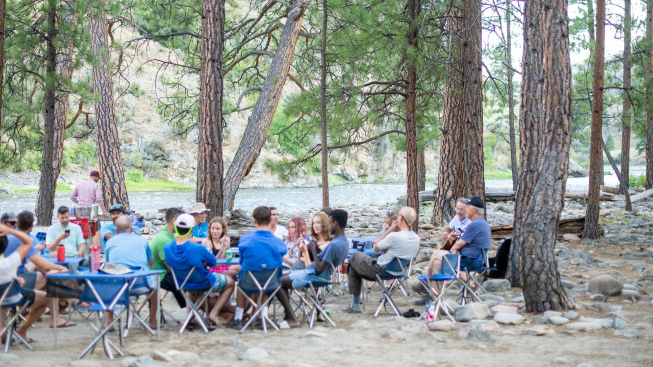 group sitting at tables along salmon river in Idaho