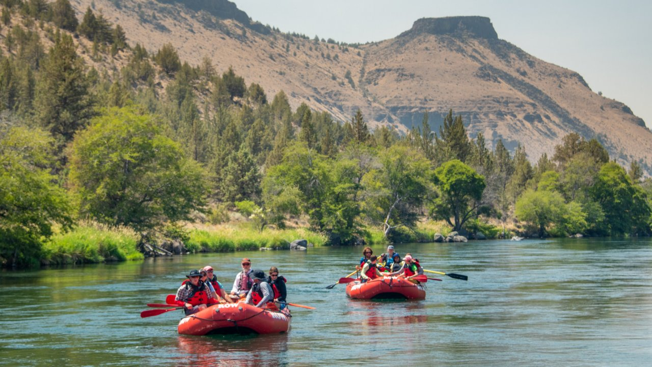 three rafts floating along the deschutes river in oregon