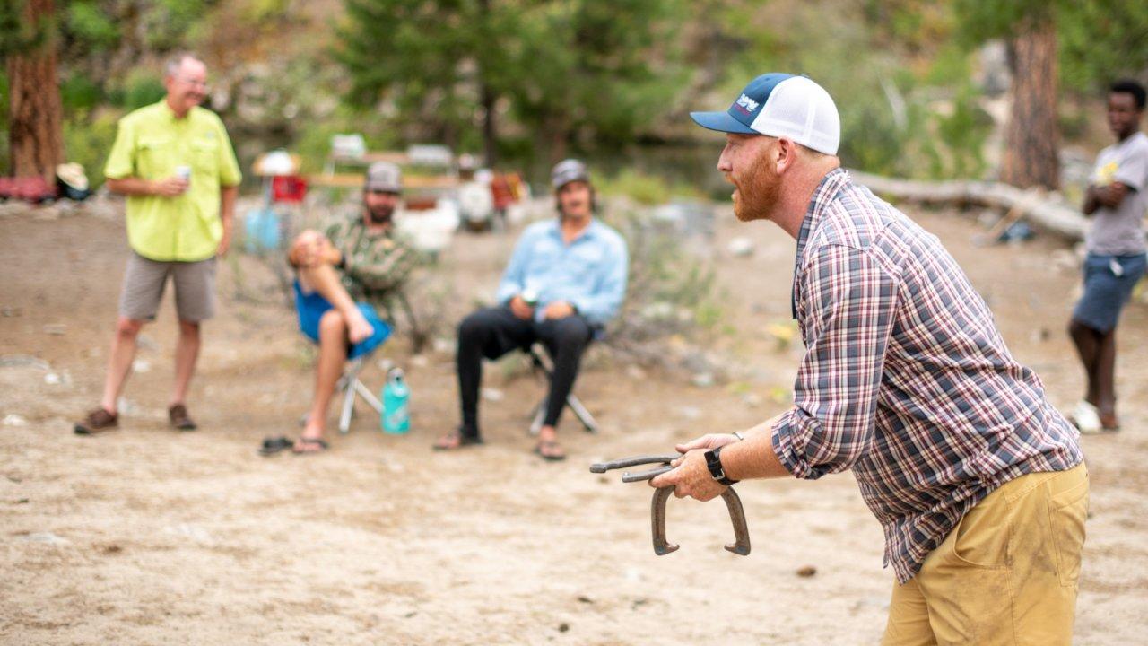 man playing horseshoes at camp