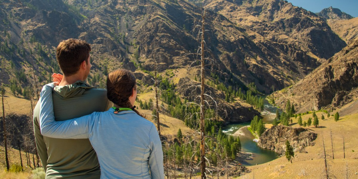 A couple overlooks the Salmon River from a vantage point along a riverside hiking trail